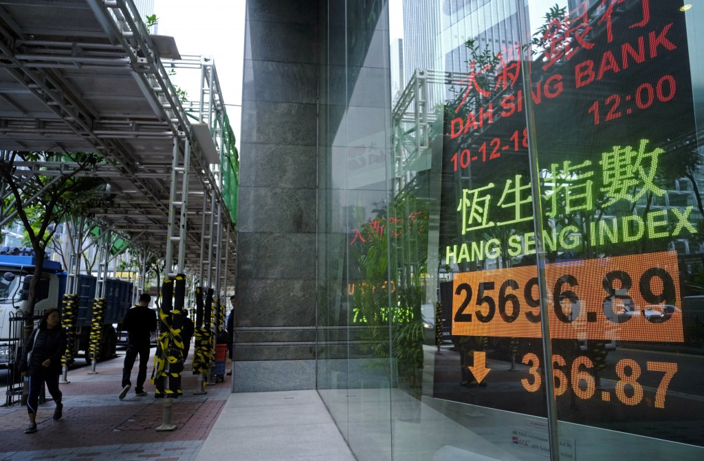 People walk past an electronic board showing Hong Kong share index outside a local bank in Hong Kong, Monday, Dec. 10, 2018. Asian markets were broadl...