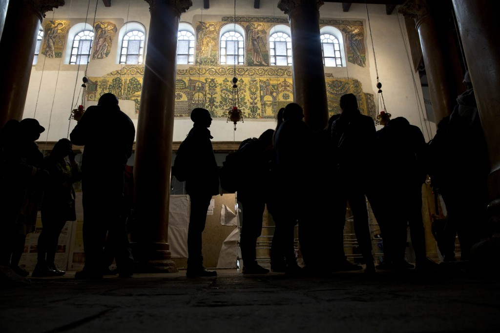 In this Thursday, Dec. 6, 2018 photo, visitors stand bellow a renovated part of a fresco inside the Church of the Nativity, built atop the site where