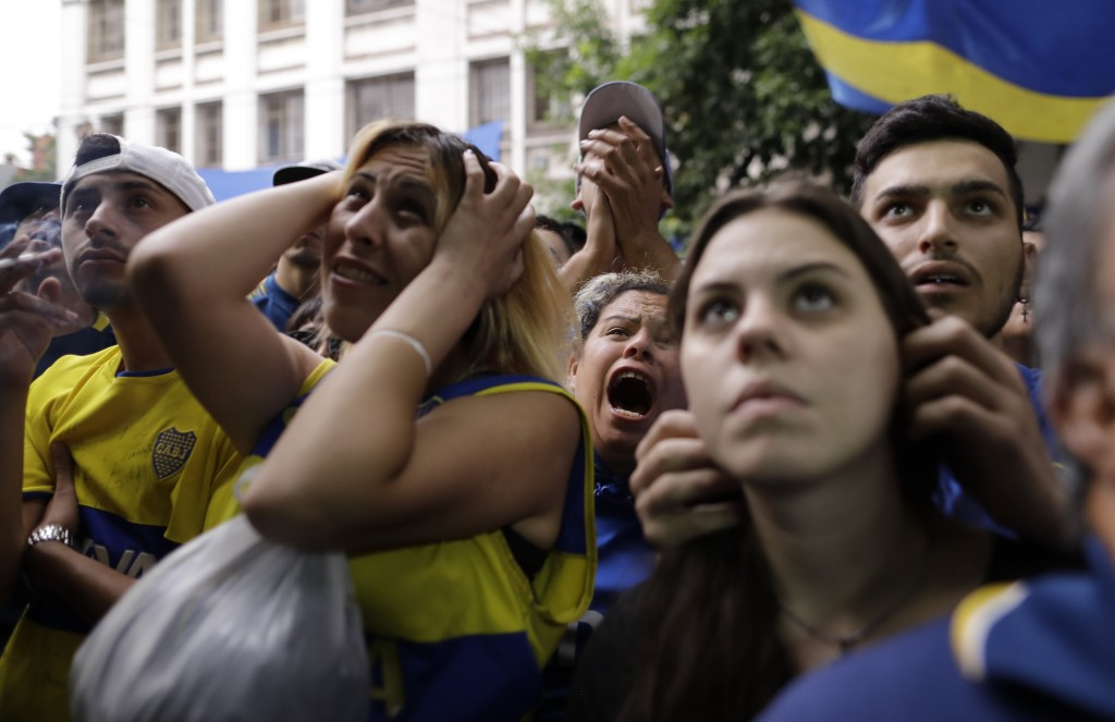 Boca Juniors soccer fans react to losing to River Plate as they watch on TV the Copa Libertadores final in Buenos Aires, Argentina, Sunday, Dec. 9, 20