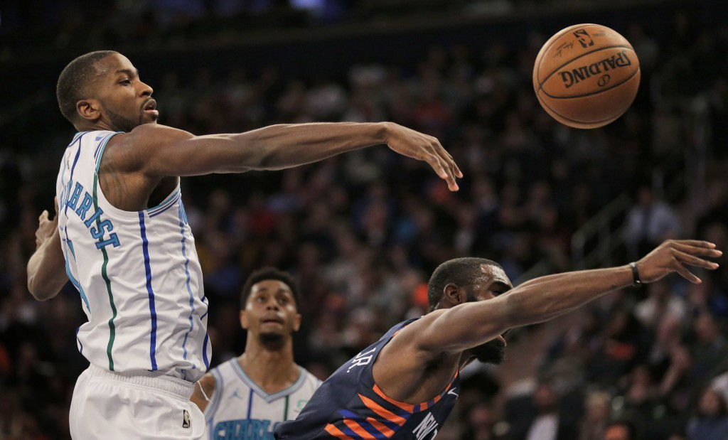 Charlotte Hornets' Michael Kidd-Gilchrist, left, gets his hand on a shot put up by New York Knicks' Tim Hardaway Jr., right, during the second half of