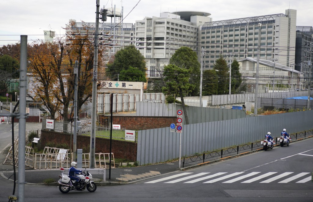 Police motorcycles pass by Tokyo Detention Center, background, where former Nissan chairman Carlos Ghosn is being detained, Monday, Dec. 10, 2018, in ...