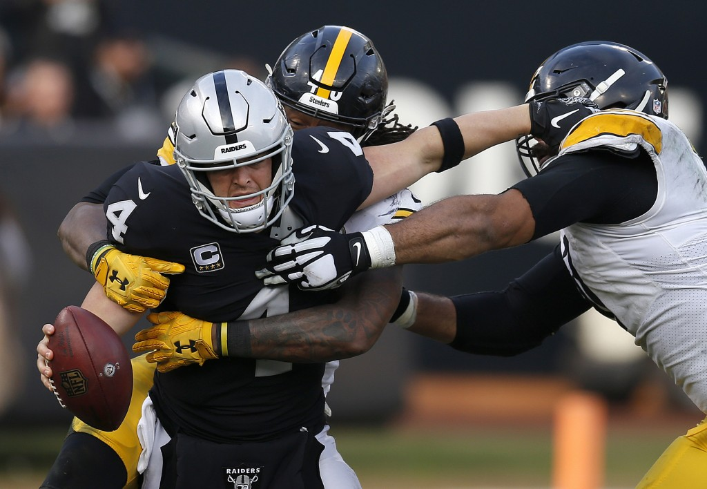Oakland Raiders quarterback Derek Carr (4) is sacked by Pittsburgh Steelers outside linebacker Bud Dupree, rear, as defensive end Cameron Heyward, rig