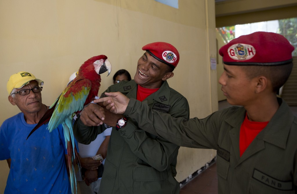Presidential guards play with a school's parrot mascot as they wait to cast their ballots at a school serving as a voting center in Caracas, Venezuela...