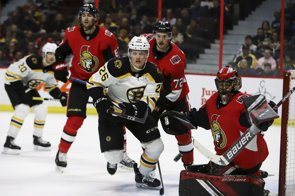Boston Bruins centre Colby Cave (26) skates towards a puck flying wide of Ottawa Senators goaltender Mike McKenna (33) during first period NHL hockey ...