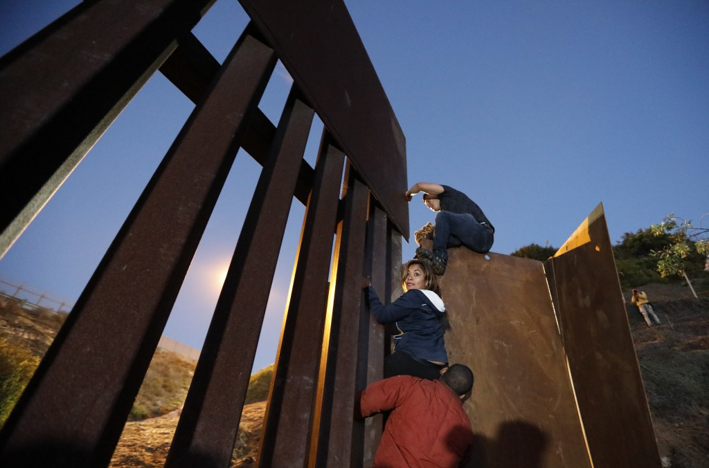 Central American migrants planning to surrender to U.S. border patrol agents climb over the U.S. border wall from Playas de Tijuana, Mexico, late Mond
