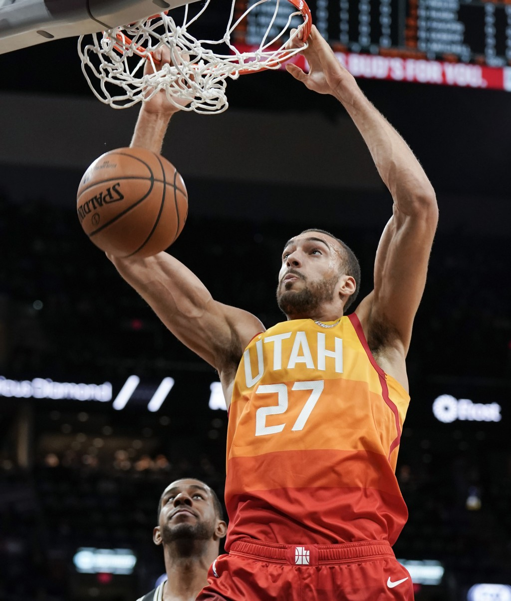 Utah Jazz center Rudy Gobert (27) dunks as San Antonio Spurs forward LaMarcus Aldridge watches during the first half of an NBA basketball game, Sunday
