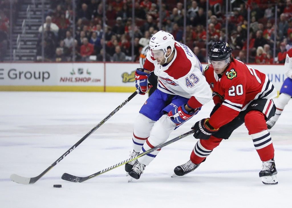Montreal Canadiens center Michael Chaput (43) battles for the puck with Chicago Blackhawks left wing Brandon Saad (20) during the first period of an N...