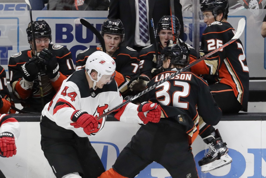 New Jersey Devils left wing Miles Wood, left, checks Anaheim Ducks defenseman Jacob Larsson during the second period of an NHL hockey game in Anaheim,