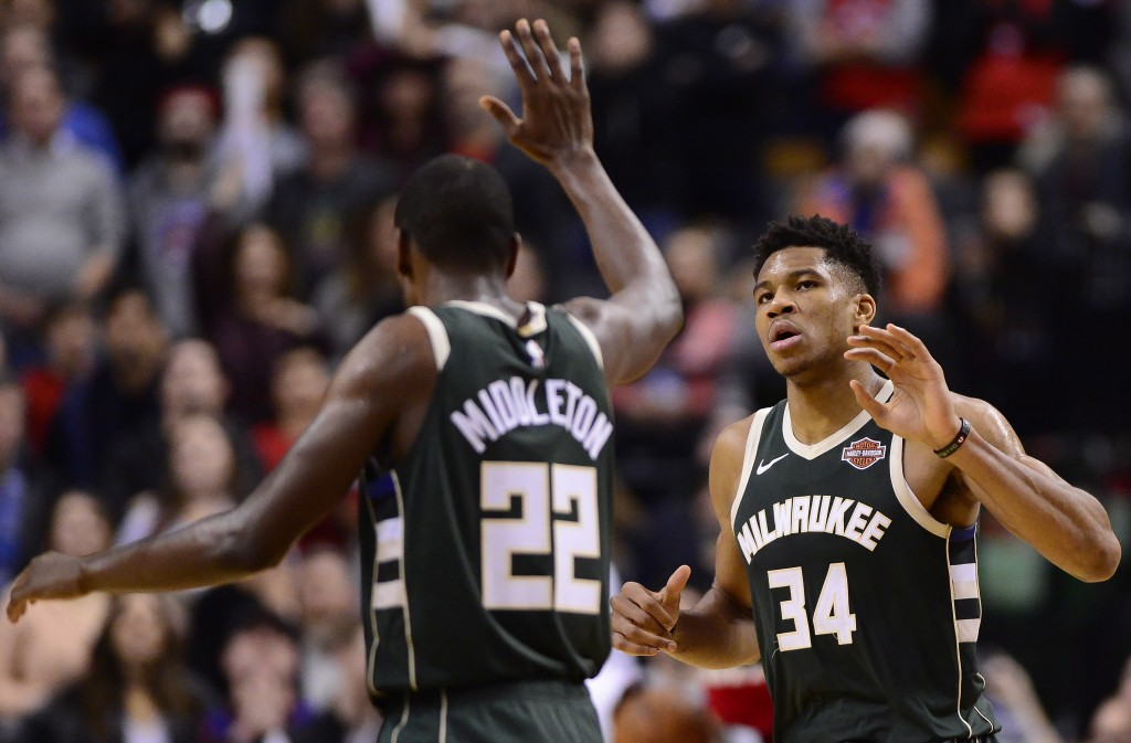 Milwaukee Bucks forward Khris Middleton (22) congratulates teammate Giannis Antetokounmpo (34) on his basket during second half NBA basketball action