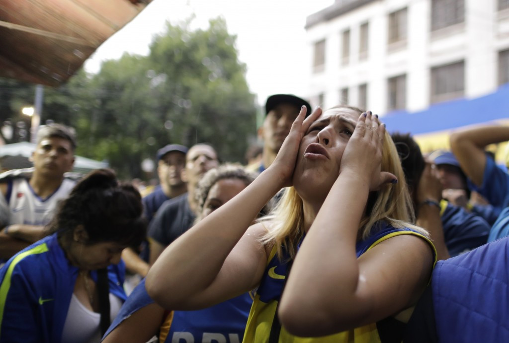 A Boca Juniors soccer fan reacts to losing 3-1 to River Plate as she watches on TV the Copa Libertadores final in Buenos Aires, Argentina, Sunday, Dec...