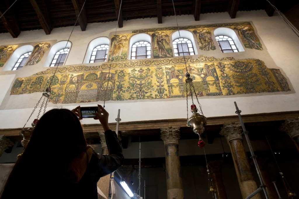 In this Thursday, Dec. 6, 2018 photo, a visitor photographs a renovated part of a fresco inside the Church of the Nativity, built atop the site where