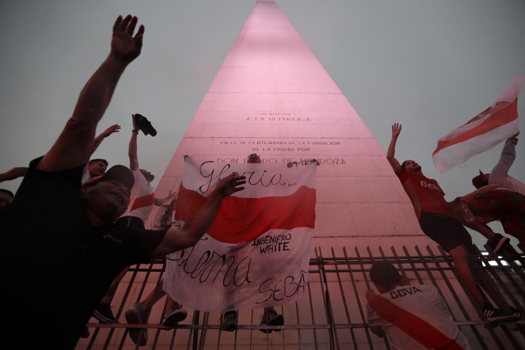 River Plate soccer fans celebrate defeating Boca Juniors 3-1 and clenching the Copa Libertadores championship title, at the Obelisk in Buenos Aires, A...