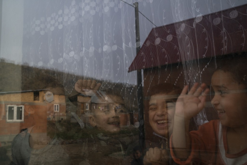 In this Nov. 14, 2018, photo, homes are reflected off the window of Monika Krcova's house as her grandchildren play inside at the Podhorany village ne...