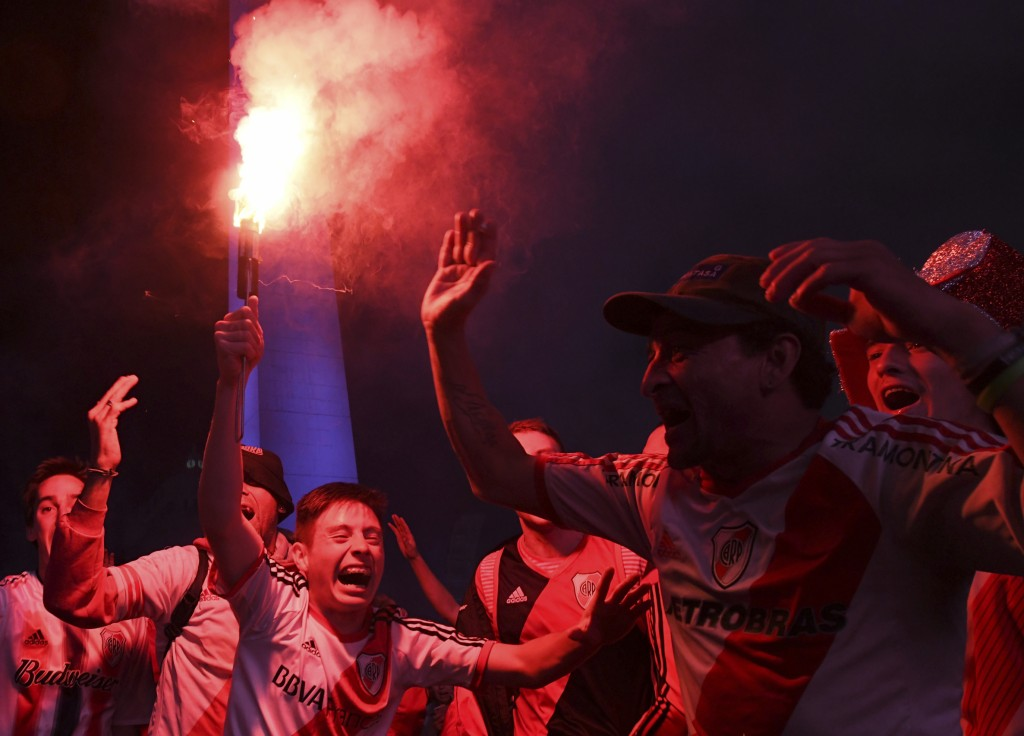 River Plate soccer fans light flares as they celebrate defeating Boca Juniors 3-1 and clenching the Copa Libertadores championship title, at the Obeli...