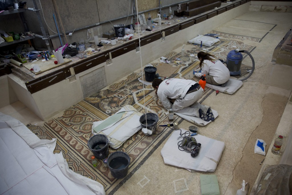 In this Thursday, Dec. 6, 2018 photo, restoration experts work on a mosaic inside the Church of the Nativity, built atop the site where Christians bel...