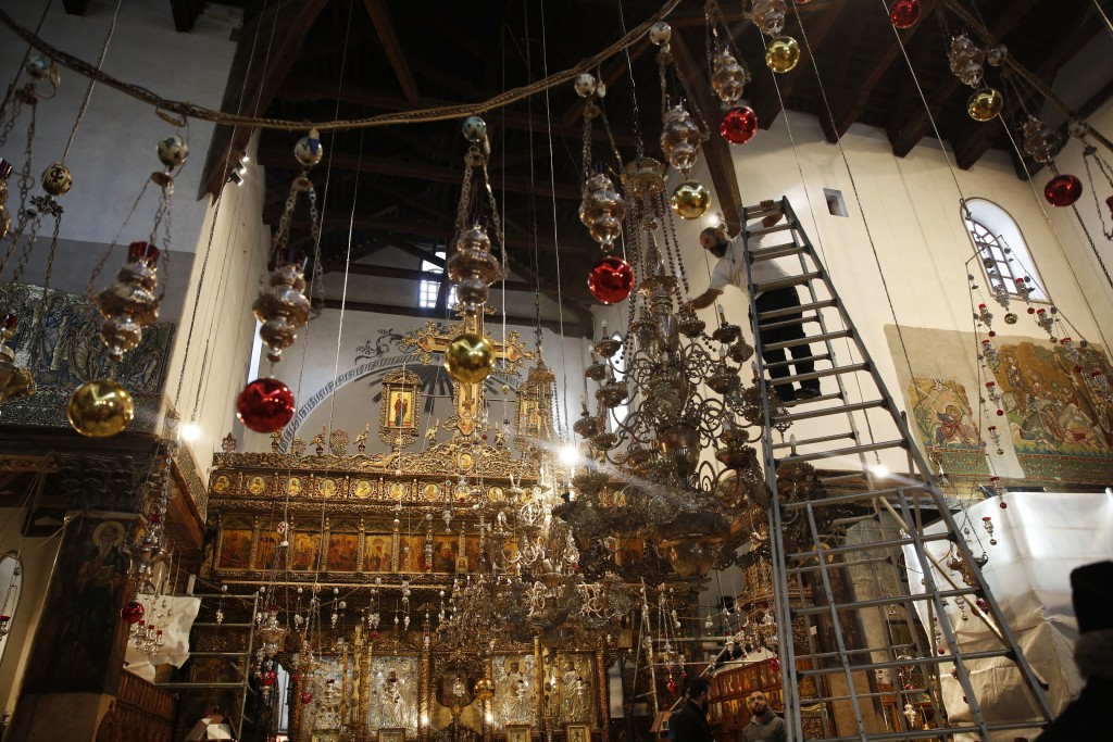 In this Wednesday, Dec. 5, 2018 photo, a worker cleans the dust from a chandelier at the Church of the Nativity, built atop the site where Christians ...