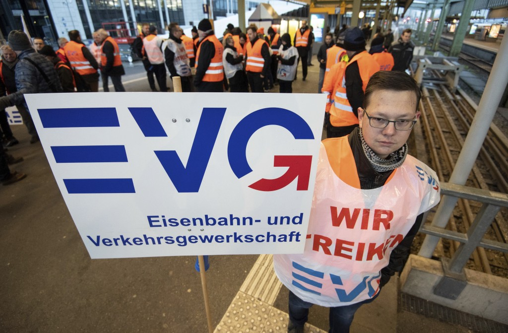 A picketer holds a poster of the train workers union at the main station in Stuttgart, southern Germany, Monday, Dec. 10, 2018. Thousands of commuters
