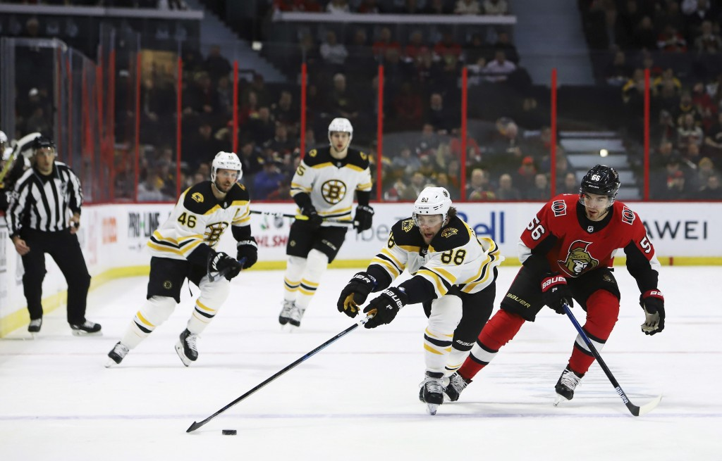 Boston Bruins right wing David Pastrnak (88) reaches far for the puck under pressure from Ottawa Senators left wing Magnus Paajarvi (56) during first-