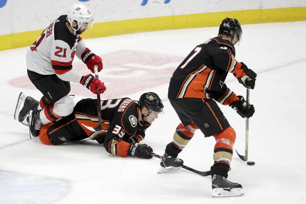 Anaheim Ducks left wing Andrew Cogliano, from right, right wing Jakob Silfverberg vie for the puck against New Jersey Devils right wing Kyle Palmieri