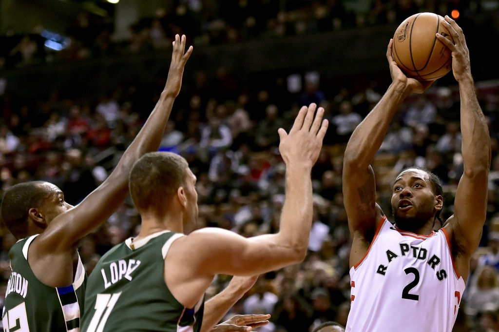 Toronto Raptors forward Kawhi Leonard (2) looks to shoot as Milwaukee Bucks center Brook Lopez (11) and forward Khris Middleton (22) defend during fir...