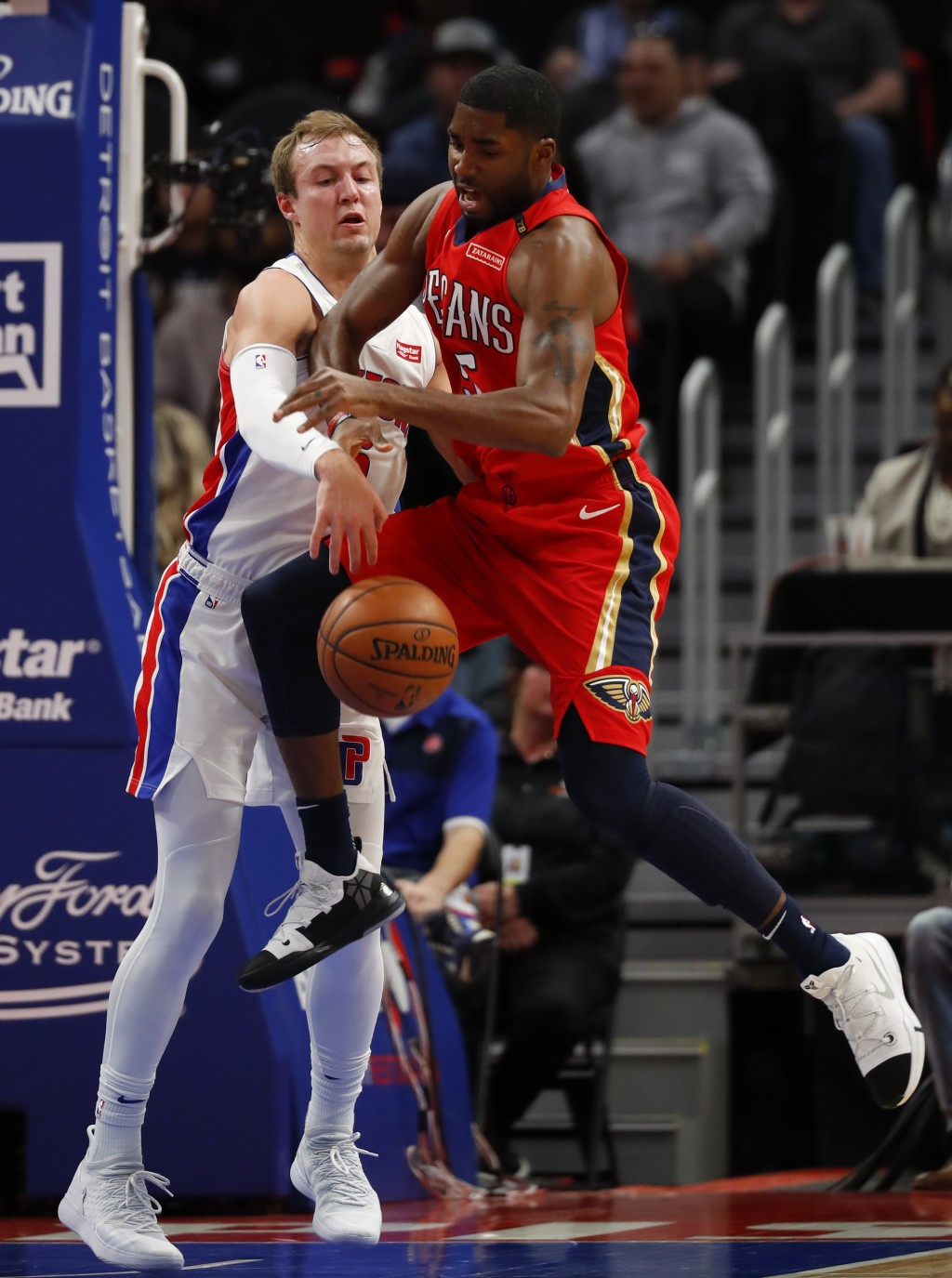 Detroit Pistons guard Luke Kennard, left, knocks the ball from New Orleans Pelicans guard E'Twaun Moore, right, in the first half of an NBA basketball...