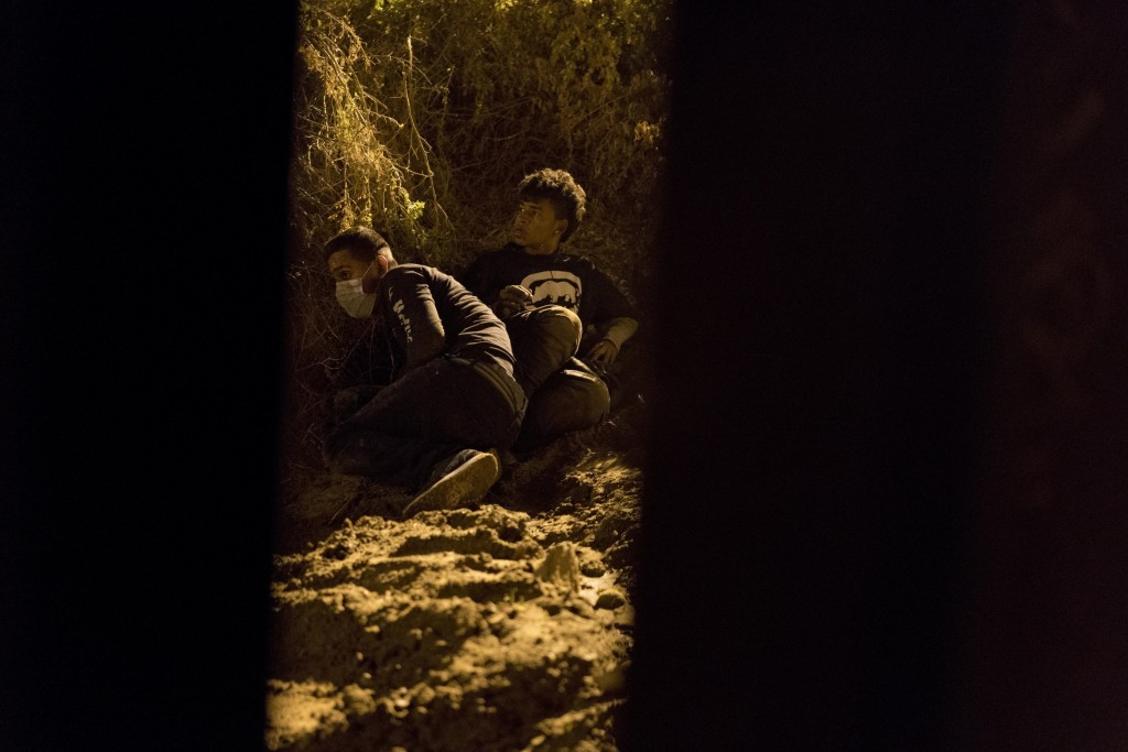 Salvadoran migrant Cesar Jobet, right, and Daniel Jeremias Cruz hide from U.S. border agents after they dug a hole in the sand under the border wall a