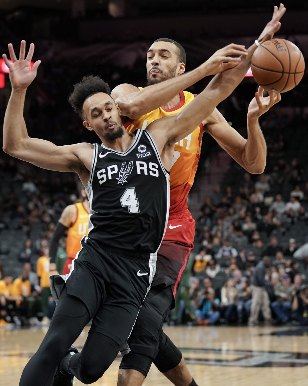 Utah Jazz center Rudy Gobert, right, collides with San Antonio Spurs guard Derrick White during the first half of an NBA basketball game, Sunday, Dec....