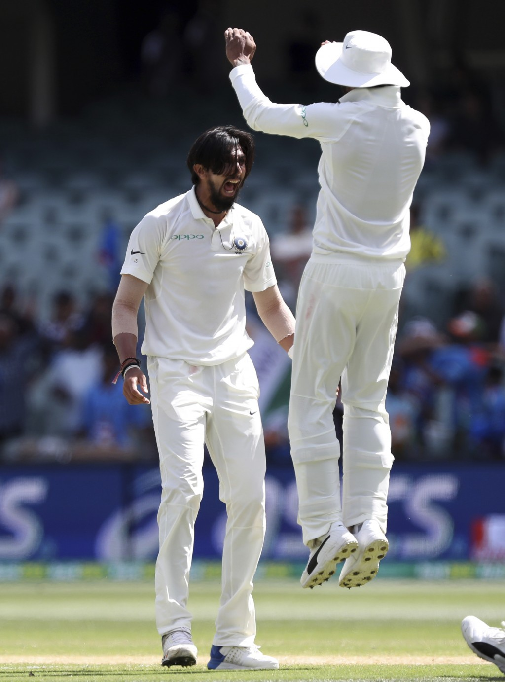 India's Ishant Sharma, left, celebrates with a teammate after taking the wicket of Australia's Travis Head on the final day of the first cricket test ...