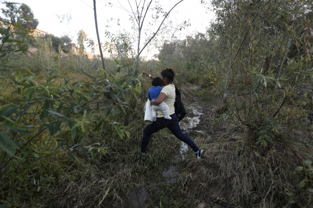 Yesenia Martinez, 24, carries her eight-month-old son Daniel as she looks for a place to cross the U.S. border wall to surrender to border patrol and