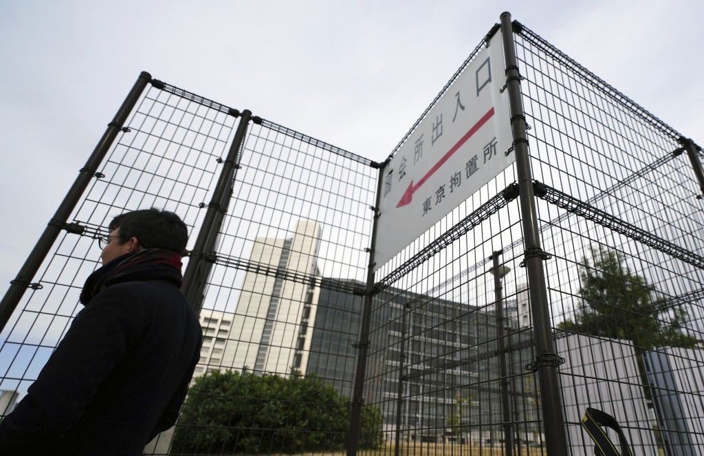 A journalist stands outside Tokyo Detention Center where former Nissan chairman Carlos Ghosn is being detained, Monday, Dec. 10, 2018, in Tokyo. Tokyo...