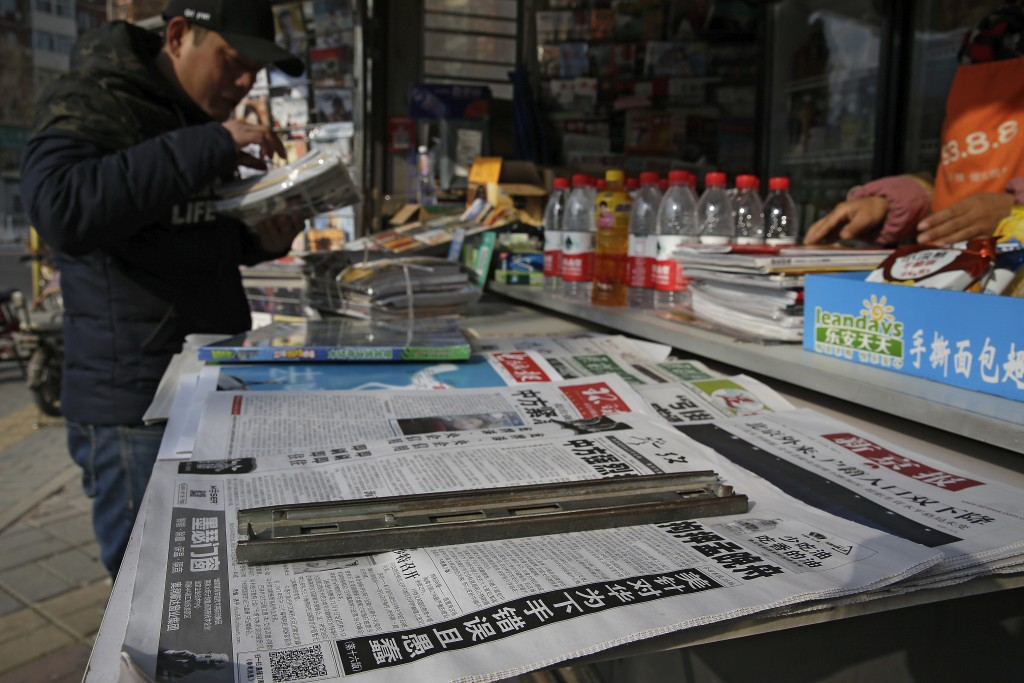 A man arranges magazines near newspapers with the headlines of China outcry against U.S. on the detention of Huawei's chief financial officer, Meng Wa...