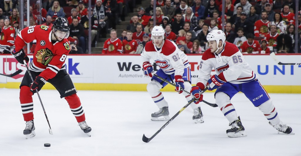 Chicago Blackhawks right wing Patrick Kane (88) is defended by Montreal Canadiens right wing Andrew Shaw (65) and center Jonathan Drouin (92) during t...