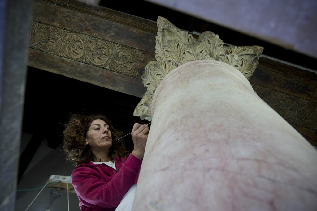 In this Thursday, Dec. 6, 2018 photo, a restoration expert works on a granite column inside the Church of the Nativity, built atop the site where Chri