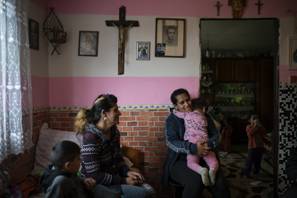 In this Nov. 14, 2018, photo, Monika Krcova, center left, sits with her daughter Ivana and her grandchildren in their house in Podhorany village, near...
