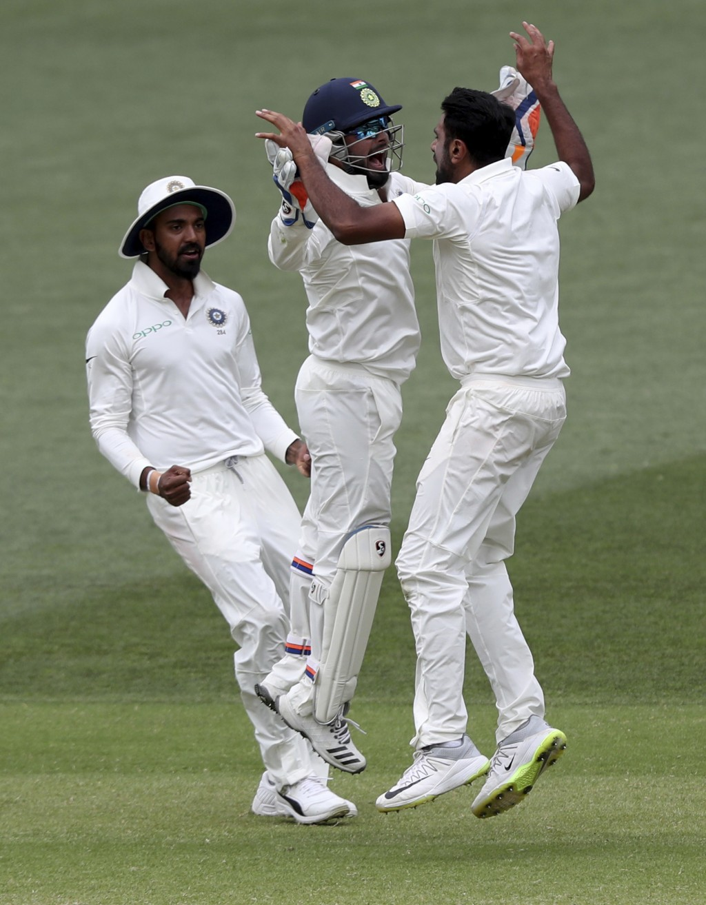 India's Ravi Ashwin, right, celebrates with teammate Rishabh Pant after taking the wicket of Australia's Josh Hazlewood to win the first cricket test