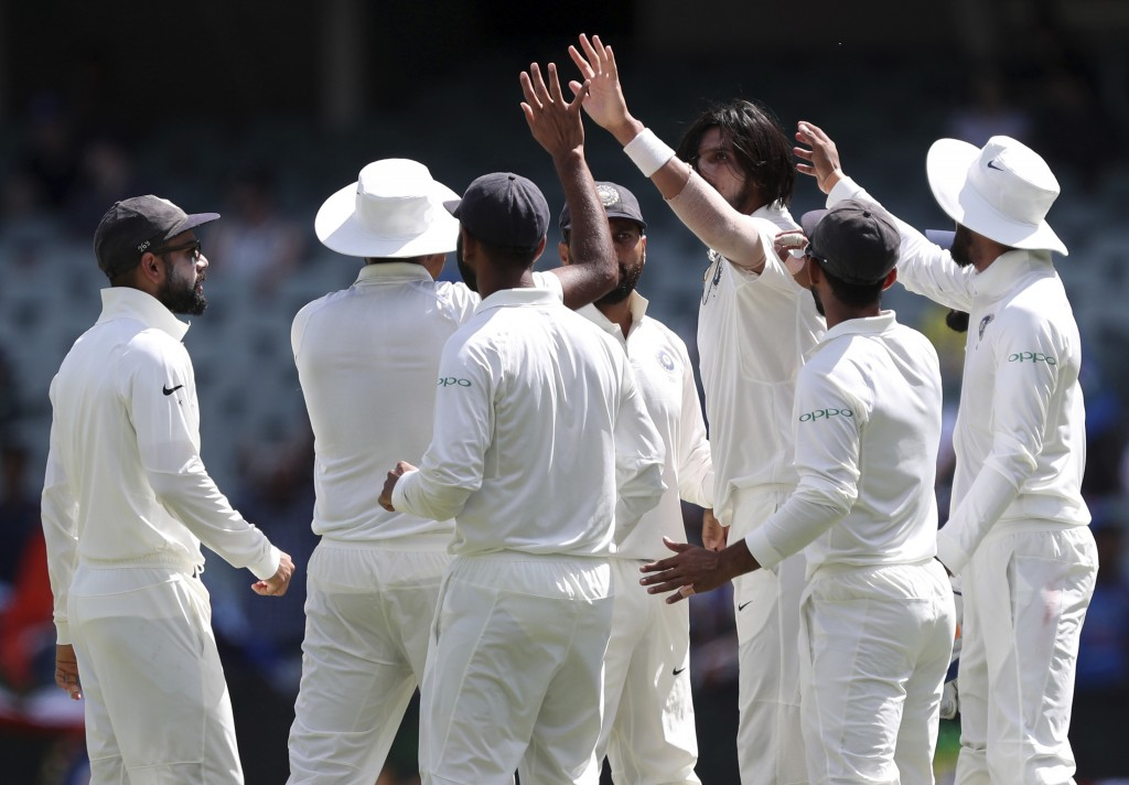 India's Ishant Sharma, third right, celebrates with his teammates after taking the wicket of Australia's Travis Head on the final day of the first cri...