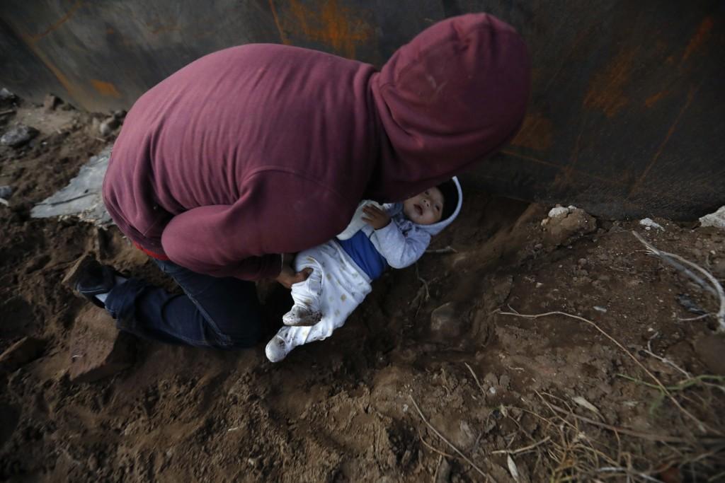 Honduran migrant Joel Mendez, 22, passes his eight-month-old son Daniel through a hole under the U.S. border wall to his partner, Yesenia Martinez, 24