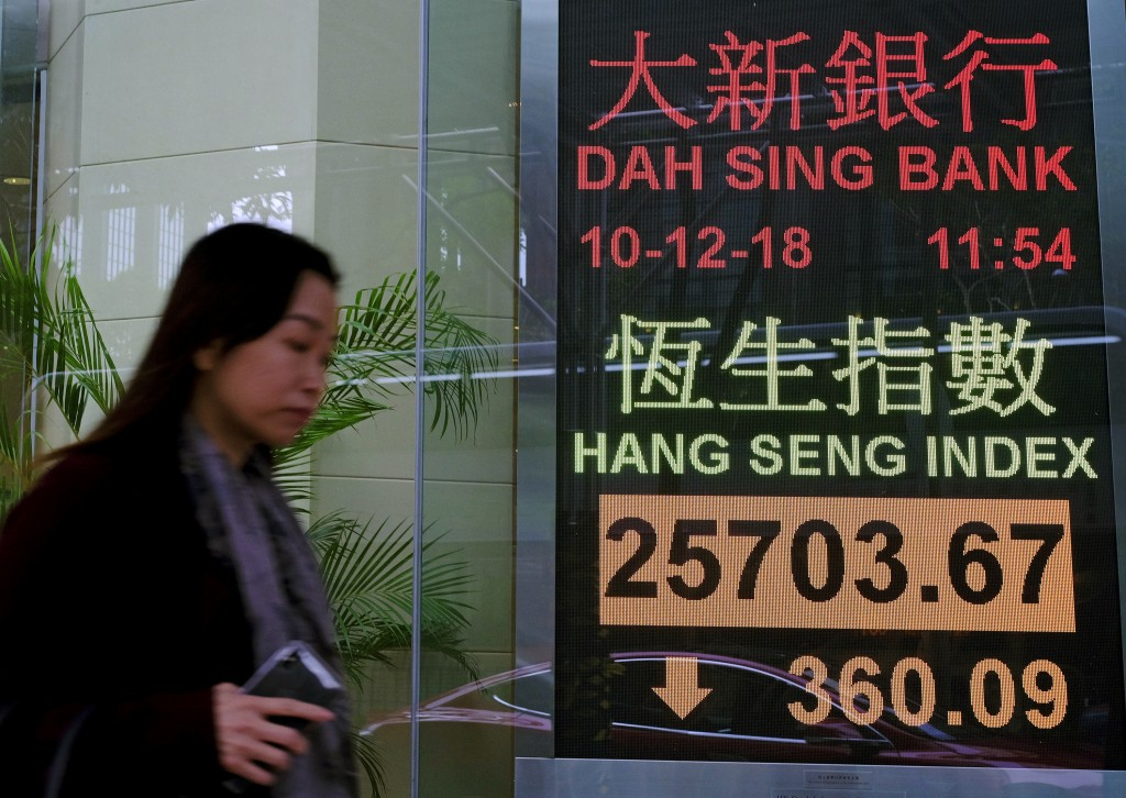 A woman walks past an electronic board showing Hong Kong share index outside a local bank in Hong Kong, Monday, Dec. 10, 2018. Asian markets were broa...