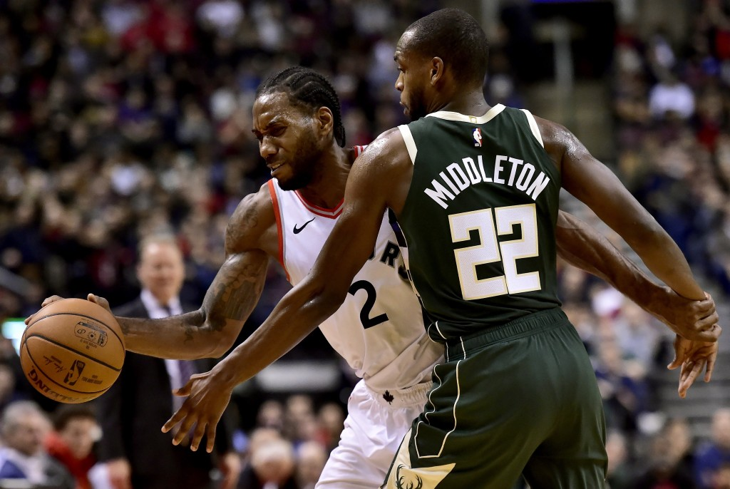 Milwaukee Bucks forward Khris Middleton (22) fouls Toronto Raptors forward Kawhi Leonard (2) during second half NBA basketball action in Toronto on Su