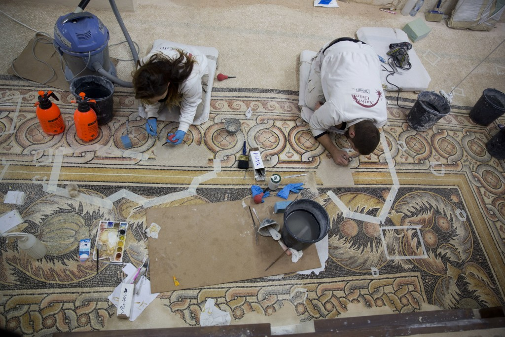 In this Thursday, Dec. 6, 2018 photo, restoration experts work on a mosaic inside the Church of the Nativity, built atop the site where Christians bel