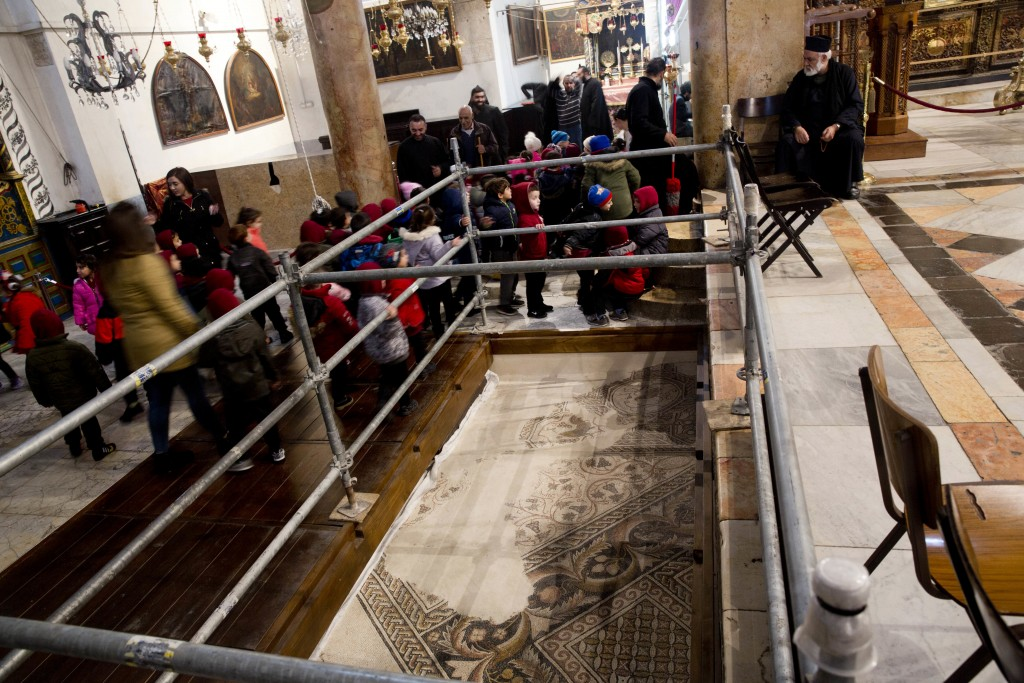 In this Thursday, Dec. 6, 2018 photo, visitors walk by a renovated part of a mosaic inside the Church of the Nativity, built atop the site where Chris...