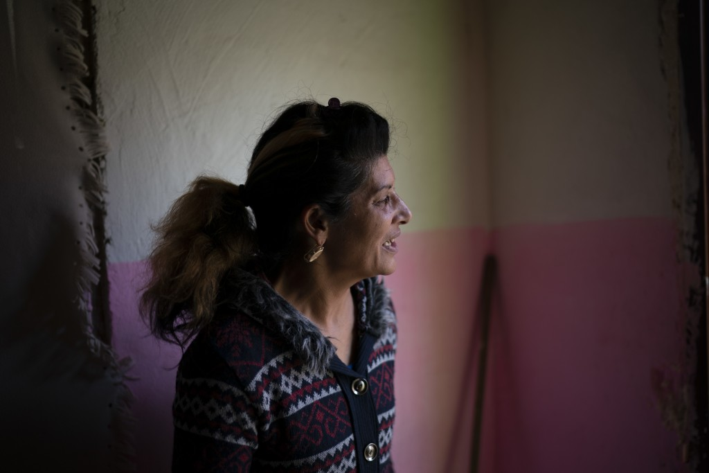 In this Nov. 14, 2018, photo, Monika Krcova talks to a neighbor while standing in her house at the Podhorany village near Kezmarok, Slovakia. Krcova d...