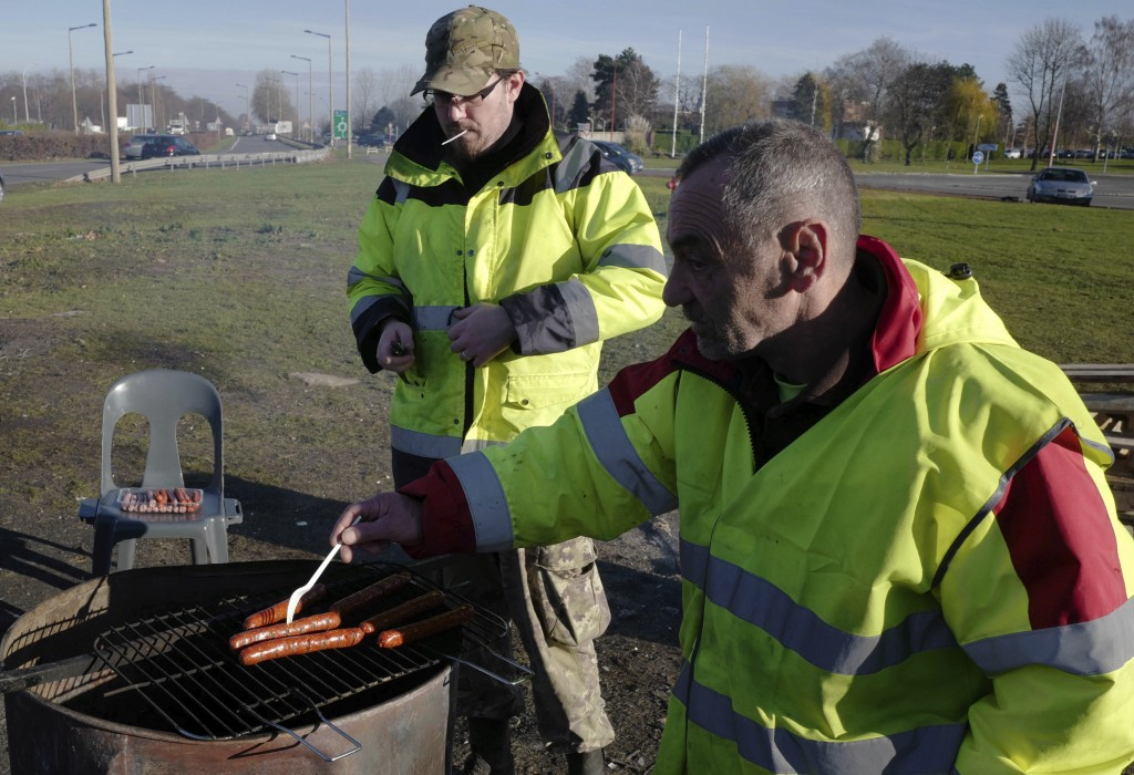 Demonstrators wearing their yellow vests prepare sausages for lunch on a traffic circle, Tuesday, Dec. 11, 2018 in Douai, northern France. President E