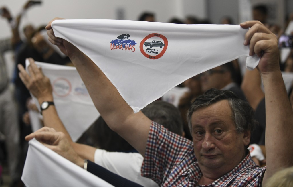 "Family members of ex-Ford Motor Co. employees hold up handkerchiefs that are stamped with a message that reads in Spanish: ""Ford never more"" in a cour"