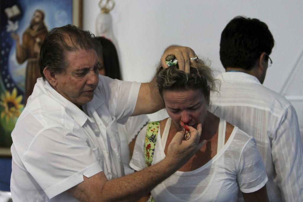 FILE -In this Feb. 23, 2012 file photo, self-styled spiritual healer Joao Teixeira de Faria uses scissors to perform a spiritual surgery on Rosangela