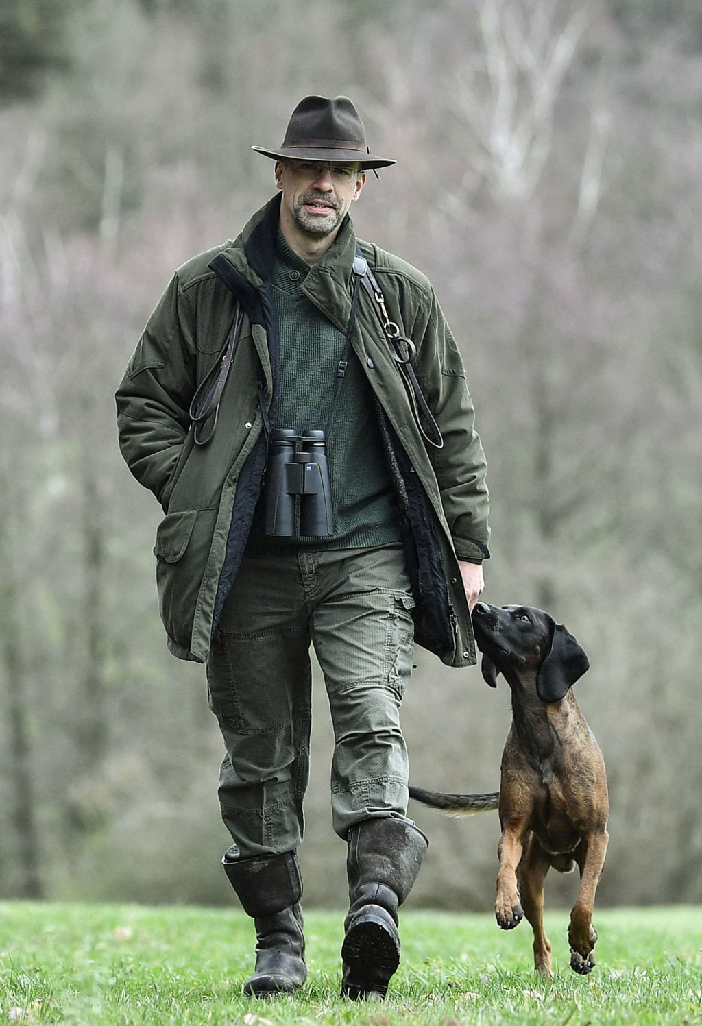 In this Dec. 7, 2018 photo Dirk Gratzel walks with his dog at his hunting ground in Stollberg, western Germany. Gratzel counts his carbon emissions. T...