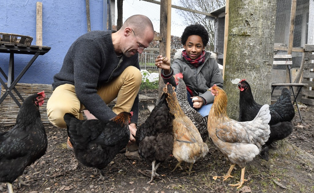 In this Dec. 7, 2018 photo Dirk Gratzel, left, and neighbor kid Elias feed their chicken in Stollberg, western Germany. Gratzel counts his carbon emis...