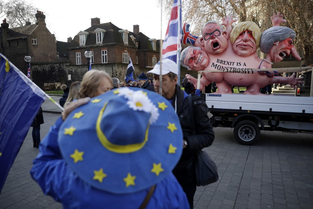 A remain in the European Union, anti-brexit sculpture is displayed as a protester wearing a European flag design hat stands demonstrating in the foreg