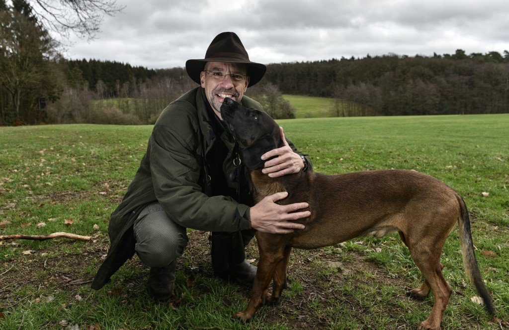 In this Dec. 7, 2018 photo Dirk Gratzel poses for a photo with his dog at his hunting ground in Stollberg, Germany. Gratzel counts his carbon emission...