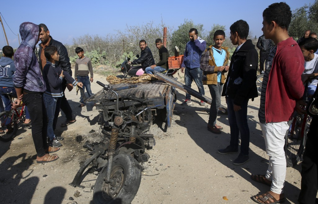 FILE - In this Monday, Nov. 12, 2018 file photo, Palestinians inspect a vehicle that was destroyed in an Israeli raid that killed seven Hamas Palestin